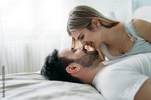Leinwanddruck Bild Portrait of young loving couple in bedroom