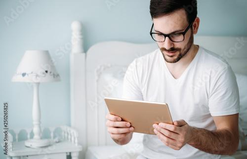 Foto Murales Handsome man using digital tablet in bedroom