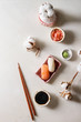 Sushi Set nigiri with salmon and butterfish in pink ceramic serving plate, chopsticks, bowls of soy sauce, and pickled ginger, cotton flowers over white marble background. Flat lay, space. Japan menu