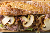 Close up of beef baguette sandwich with champignon mushrooms, green salad, fried onion. Flat lay, space