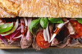 Close up of beef baguette sandwich with tomatoes, basil, red onion. Flat lay, space