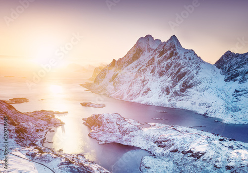 Leinwandbild Motiv Aerial view at the Lofoten islands, Norway. Mountains and sea during sunset. Natural landscape from air at the drone. Norway at the winter time