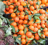 many orange tangerines with green leaves