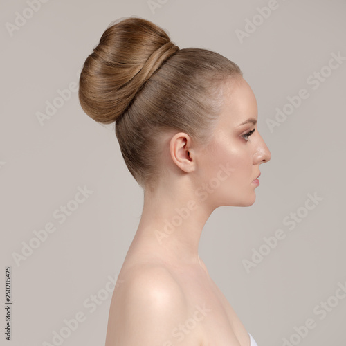 Portrait of a beautiful young woman with a creative haircut, a bunch of hair. Brown hair