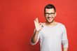 Happy handsome man showing ok sign. Isolated over red background.