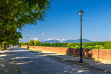 Pedestrian walking path street with lamps on defensive city wall in clear sunny day with Tuscany hills and mountains and clear blue sky background, Lucca, Italy