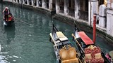 A channel with two gondolas and a gondolier floating near them in Venice, Italy.