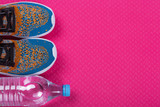 sports concept, colored sneakers and a water bottle on a pink fitness mat