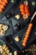 Fresh sushi rolls on black slate. Restaurant table setting.