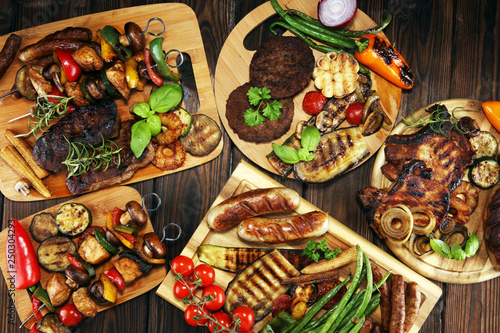 Assorted delicious grilled meat with vegetable on rustic table - 250304293