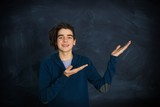 portrait of smiling teenager pointing - 250314009