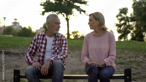 Leinwanddruck Bild Offended senior couple sitting on bench and looking at each other, relationships