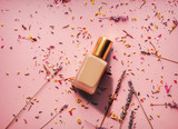 golden nail polish and lavender petals on pink background