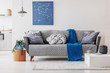 Blue blanket and grey knot pillow on trendy sofa in chic living room