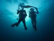 Young woman and man scuba divers exploring
