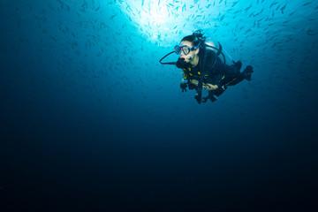 Young woman scuba diver exploring coral reef © Jag_cz