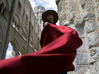 Femme agitant une soie rouge dans les ruines d'une église du mayen-âge