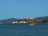 a cute small yellow ferry sails past alcatraz island in san francisco