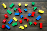 Children background. Wooden building blocks for developing and entertainment on dark wooden background top view