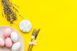 Easter table setting. Tableware and painted eggs on yellow background top view copy space
