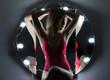 Leinwanddruck Bild - junge Frau im roten Body vor Spiegel