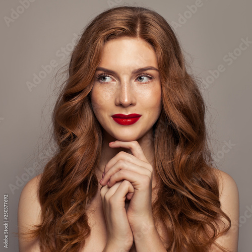 Leinwanddruck Bild Smiling red haired woman portrait. Cute redhead girl with curly hair
