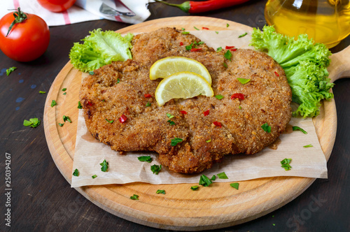 Leinwanddruck Bild Large Viennese schnitzel on a wooden board with lemon on a dark background. Meat dish