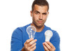 portrait of young man, holding LED bulb and old fachion bulb on white background