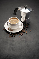 Cup of coffee and a coffee pot on a black concrete background
