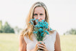Leinwanddruck Bild - Young woman with bouquet of cornflowers