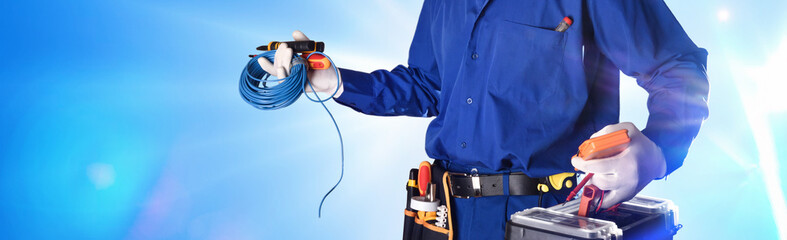 Electrician with tools and electrical equipment isolated with lights © Davizro Photography