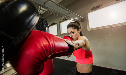 Caucasian adult woman training kickboxing at the gym