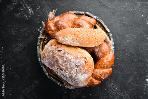 Assortment of bread and baking on a black stone background. Top view. Free space for your text.