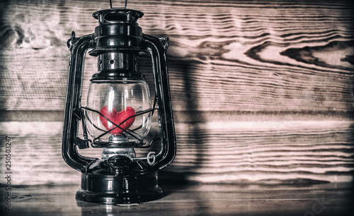 Red heart in oil lamp on wooden table. love concept. © surachat