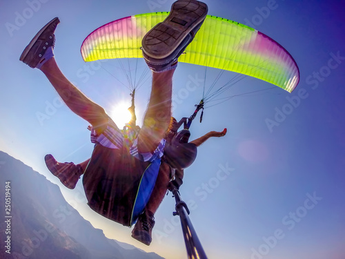 Paragliding in the sky. Paraglider tandem flying over the sea with blue water and mountains in bright sunny day. Aerial view of paraglider and Blue Lagoon in Oludeniz, Turkey. Extreme sport. Landscape © blackdiamond67