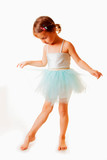 Cute little child girl in light blue dress plays in the ballet. Vertical image.