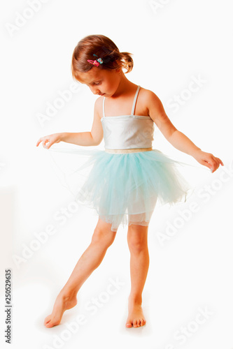 Cute little child girl in light blue dress plays in the ballet. Vertical image. © zwiebackesser