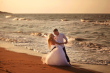 happy beautiful young couple in wedding dress and suit by the sea at sunset, waves