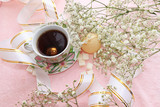 cup of coffee and flowers in festive packaging, good morning on a pink background in a cozy home