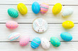 Easter symbols. Colorful Easter eggs and gingerbread on white wooden background