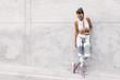 Fitness sport model in fashion sportswear posing over gray wall