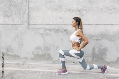Fitness sport woman in fashion sportswear doing workout over gray wall © Alena Ozerova