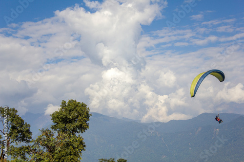 tandem paragliders in the sky against the backdrop of a misty mountain valley and heavy white clouds © Pavel