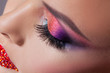 Bright eye makeup and red lips in rhinestones. Pink and blue color, colored eyeshadow.