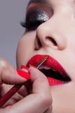 Makeup artist doing lips makeup. Apply lipstick by a brush. - 250584203