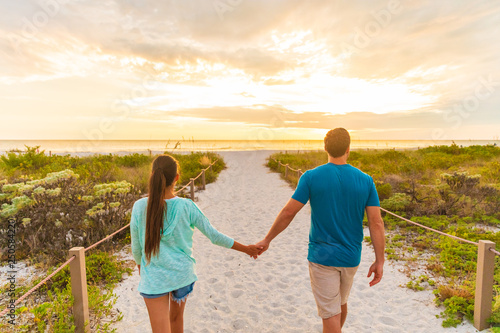 Leinwandbild Motiv Happy young couple in love walking on romantic evening beach stroll at sunset. Lovers holding hands on summer holidays in Florida beach vacation destination. People walking from behind.