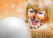 glückliches geschminktes Kind beim Kinderkarneval auf einem Freizeitpark mit einem Luftballon