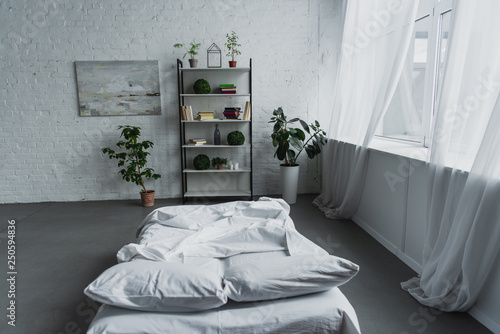 Leinwanddruck Bild modern interior design of bedroom with rack, plants, bed, brick wall and copy space