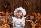 Happy baby chef, in flour, laughing, clapping, playing chef, bakery, lots of bread
