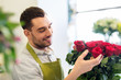 Leinwanddruck Bild - small business, sale and floristry concept - florist or seller setting red roses at flower shop